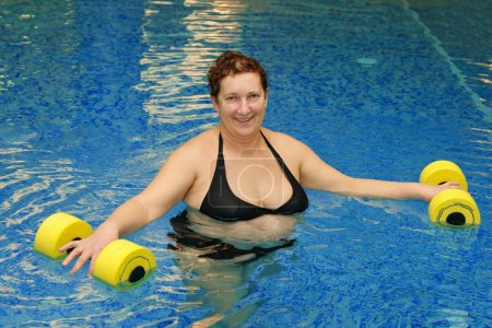 Adult woman in water with dumbbells