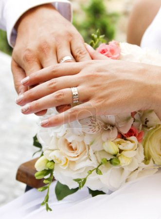 Photo for Hands and rings on wedding bouquet - Royalty Free Image