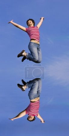 Photo for Jumping woman on a sunny day against a blue sky - Royalty Free Image