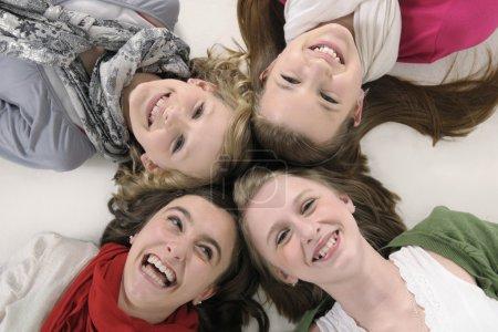 Photo pour 4 amies adolescentes allongées et souriantes à la caméra - image libre de droit
