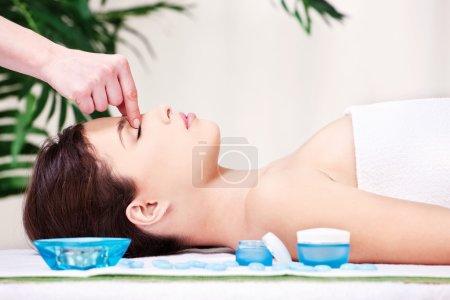 Photo pour Jolie femme sur le front massage traitement dans le salon de spa - image libre de droit