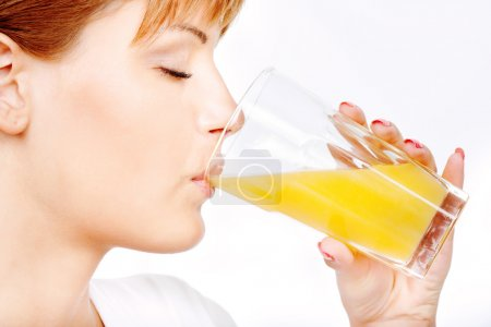 Photo for Pretty woman with eyes closed drinking orange juice - Royalty Free Image