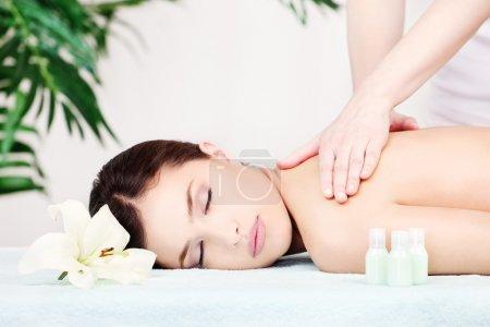 Photo pour Jolie femme sur l'épaule massage dans le salon - image libre de droit