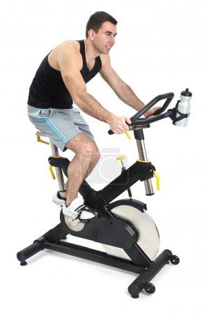 Photo for One man doing indoor biking exercise, on white background - Royalty Free Image