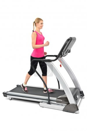 Photo for Young woman doing exercises on treadmill, on white background, some blurred motion - Royalty Free Image
