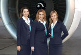 Air hostesses in front of engine