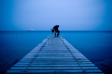 Photo for Depressed lonely man sitting on a wooden pier in the dusk - Royalty Free Image