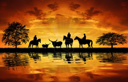 Photo for Silhouette cowboys on horses with cows in the sunset - Royalty Free Image