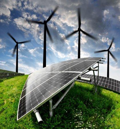 Foto de Paneles de energía solar y de la turbina de viento en la puesta del sol - Imagen libre de derechos