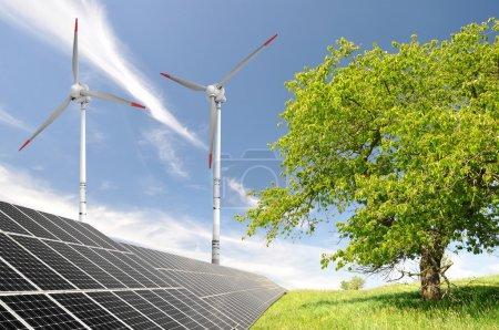 Foto de Paisaje primaveral con paneles de energía solar y turbina eólica - Imagen libre de derechos