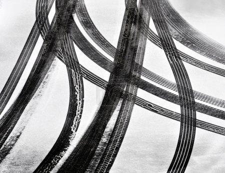 Foto de Huellas de neumáticos de coche en capa delgada de primera nieve - Imagen libre de derechos