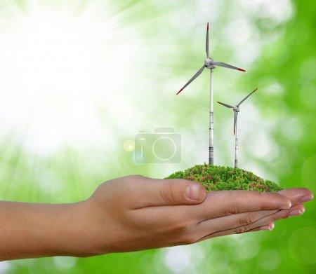 Photo pour Eolienne à la main sur fond naturel vert - image libre de droit