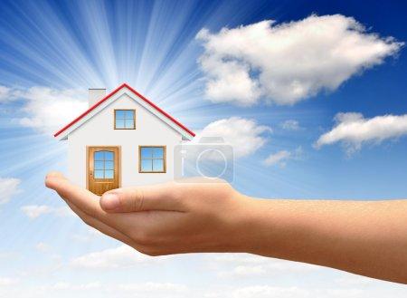 Photo pour Petite maison dans les mains contre le ciel bleu - image libre de droit
