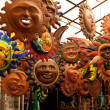 A lot of beautiful handmade masks of sun in the ha...