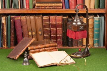 Foto de Libros de cuero antiguo, lámpara y gafas de lectura en papel secante verde. - Imagen libre de derechos