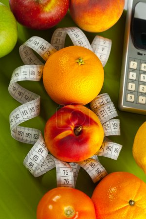 Photo for Concept of healthy food (orange, peach and tape measure) - Royalty Free Image