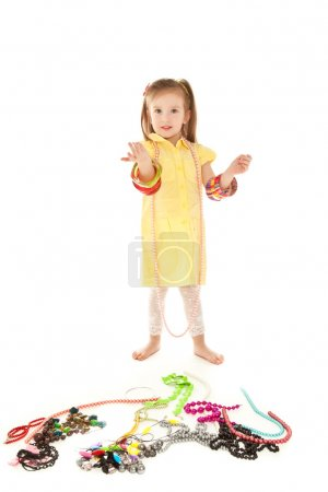 Photo for Little girl with a lot of jewel standing on the floor and smiling isolated on white - Royalty Free Image