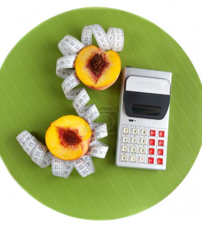 Concept of counting calories (peach, calculator and tape measur