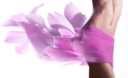 Photo pour Belle femme avec des pétales roses sur ses hanches - image libre de droit