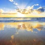 Spectacular golden sunrise over ocean with beach i...