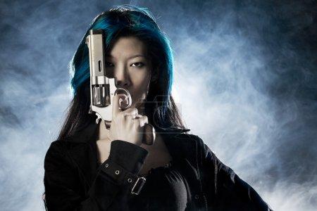 Photo pour Asiatique beauté tenant pistolet avec fumée - image libre de droit