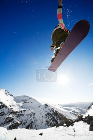 Photo for Snowboarder jumping through air with deep blue sky in background - Royalty Free Image
