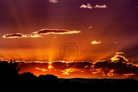 Photo for Spectacular sunset behind clouds with orange and purple sky - Royalty Free Image