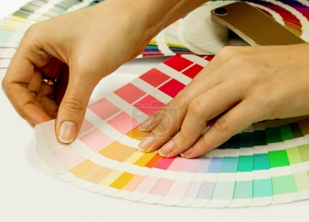 Woman selecting color from Pantone swatches book