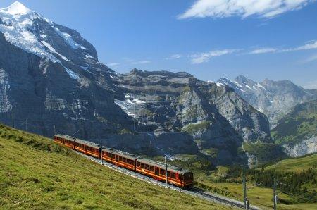Photo pour Train rouge sur fond de sommets enneigés des Alpes suisses - image libre de droit