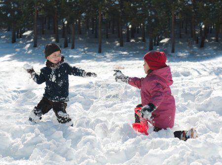 Boy and girl playing snowballs