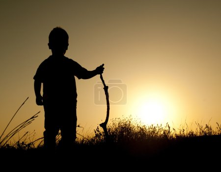 Photo pour Silhouette d'un garçon sur fond de coucher de soleil - image libre de droit
