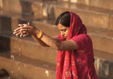 Woman making offering to the gods at Varanasi, Ind...