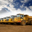 Row of yellow heavy tipper lorries...