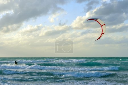 Man kite-surfing in Atlantic Ocean with dramatic weather