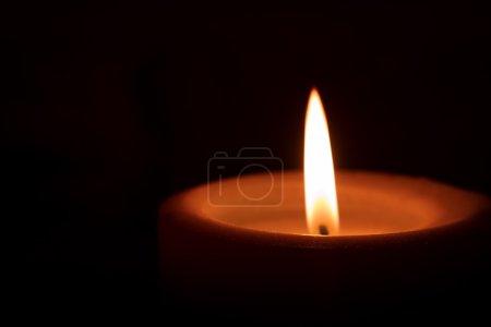 Photo pour Flamme au sommet d'une bougie pilier qui brille dans l'obscurité. Grand espace texte convivial . - image libre de droit