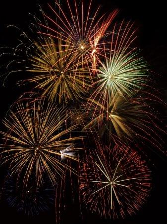 Photo pour Plusieurs explosions de feux d'artifice coloré peignent le ciel nocturne - image libre de droit