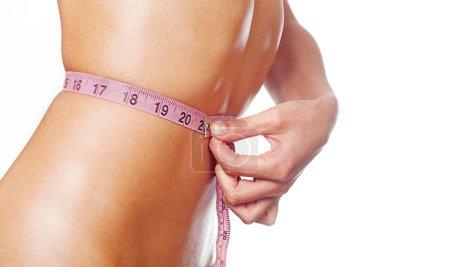 Slim young woman measuring waist.