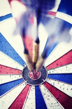 Dart in motion hitting bullseye