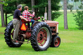 Grandfather and Grandson Driving a Vintage Tractor