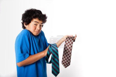 Photo pour Shoot Studio d'un garçon asiatique pensant quelle cravate pour donner à son papa - image libre de droit