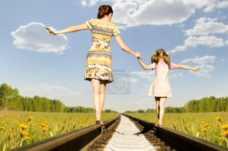 Photo for Mother with the daughter go on rails, a back to a camera, in field, in the summer - Royalty Free Image