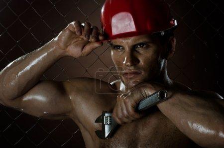 Photo pour Portrait rapproché l'ouvrier musclé de beauté, en casque de sécurité rouge avec grande clé réglable à la main, sordide et moite - image libre de droit