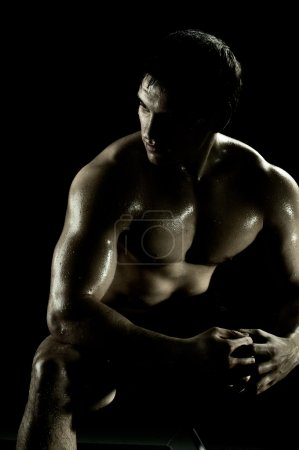 Photo for Very power athletic guy rest after execute exercise, on black background - Royalty Free Image