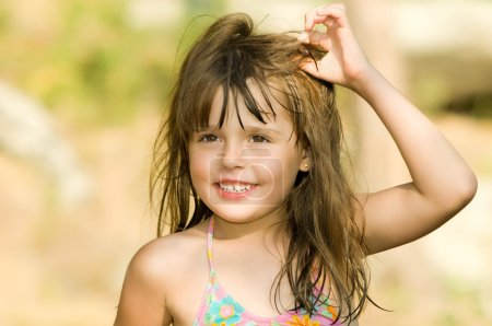 Photo for The small beautiful girl with wet tousled long hair, outdoor in a sunny day. - Royalty Free Image