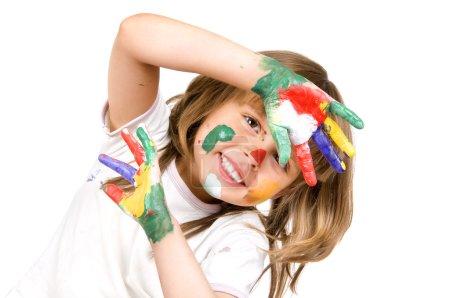 Photo pour La belle petite fille a tendu à un appareil photo d'un palmier sali dans la peinture de différentes couleurs, sourires, gros plan, sur fond blanc - image libre de droit
