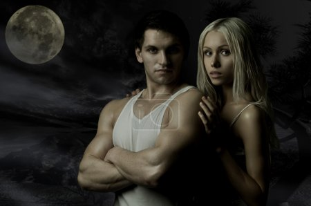 Photo for Muscular handsome sexy guy with pretty woman on dark background, look on camera - Royalty Free Image