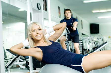 Photo for Happy cutie athletic girl , execute exercise on muscles belly and smile, in sport-hall - Royalty Free Image