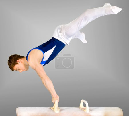Photo for The sportsman the guy, carries out difficult exercise, sports gymnastics, on white background, isolated - Royalty Free Image