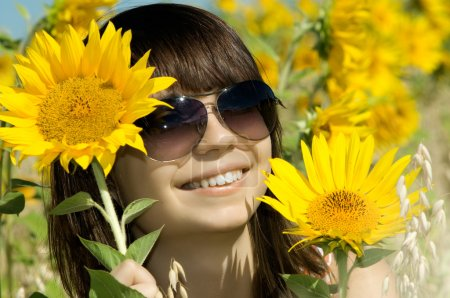 Photo for The young beautiful woman in glasses, with sunflower outdoor, smiles, face closeup - Royalty Free Image