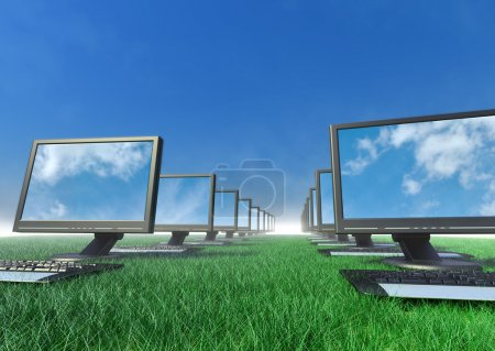 A row of computers in a field of grass.